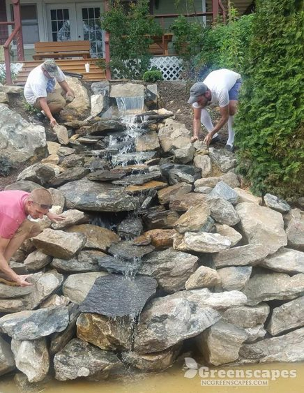 Three Greenscapes workers placing boulder stones onto flowing man made waterfall connected to pond
