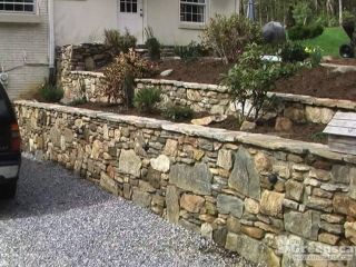 Two tiered doggett mountain stone retaining wall complete on the side of home