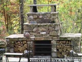 Stone outdoor fireplace with wood storage and stone patio