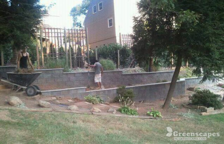 Greenscapes masonry contractor working on a cement retaining wall