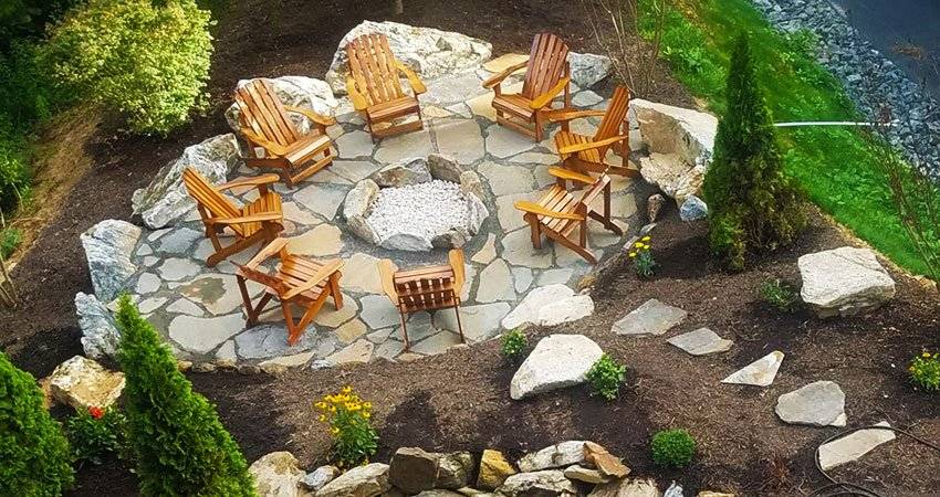 large stone pathway leading to a completed masonry construction on stone patio and firepit. Eight honey wood seating chairs sit around the fire pit