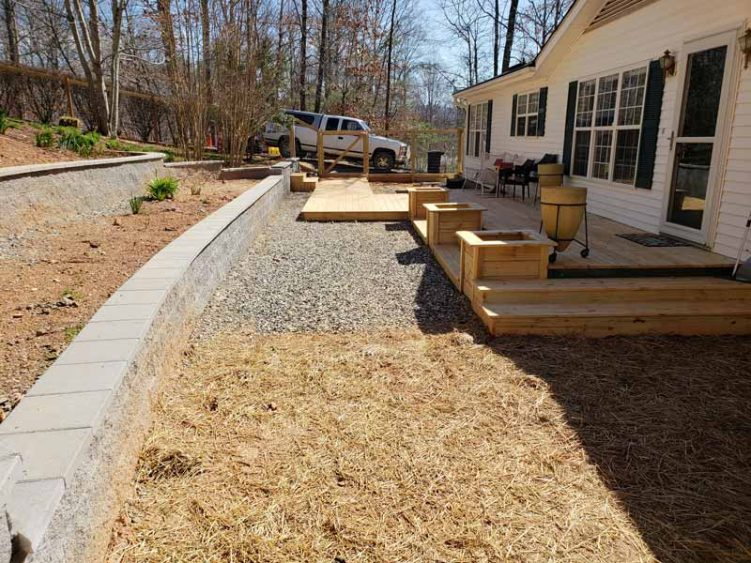 long block retaining wall with stairs and custom deck with 3 planters