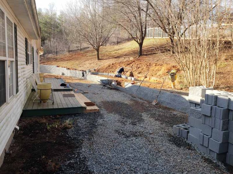 working laying brick in yard of mountain home