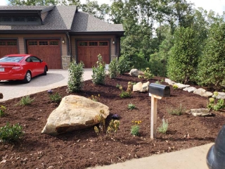 mailbox surrounded by newly laid mulch and flowers. Boulder near mailbox and beautiful wood door garage