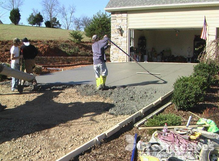 Masonry contractors building concrete driveway attached to garage