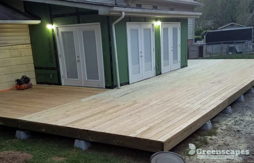 outdoor outdoor carpentry contractors built large platform deck built off of 4 double doors sun room