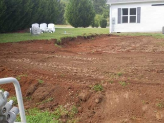 large section of yard brown dirt with green grass surrounded it