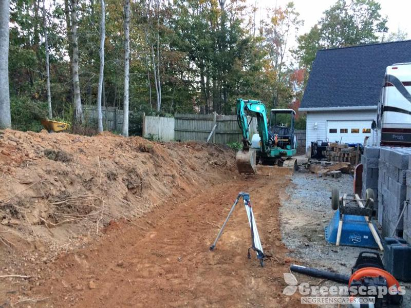 green machine grading the land and getting it ready for a retaining wall