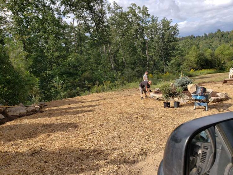 two men laying rock in a new graded yard with grass fertilization