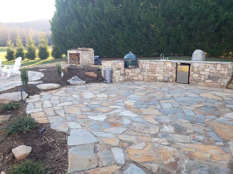 flagstone outdoor kitchen with green egg, firewood holder and firepit