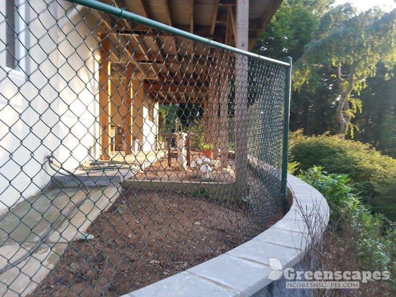green fence attached to split face retaining wall to fix clients draininage problem