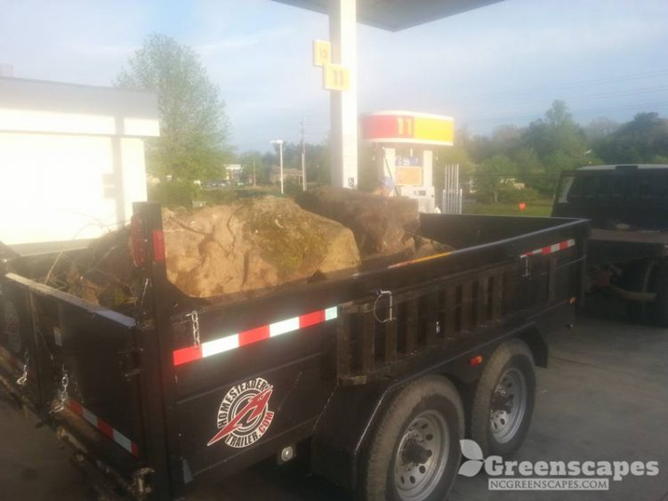 Black trailer holding large boulder rocks parked at a gas station