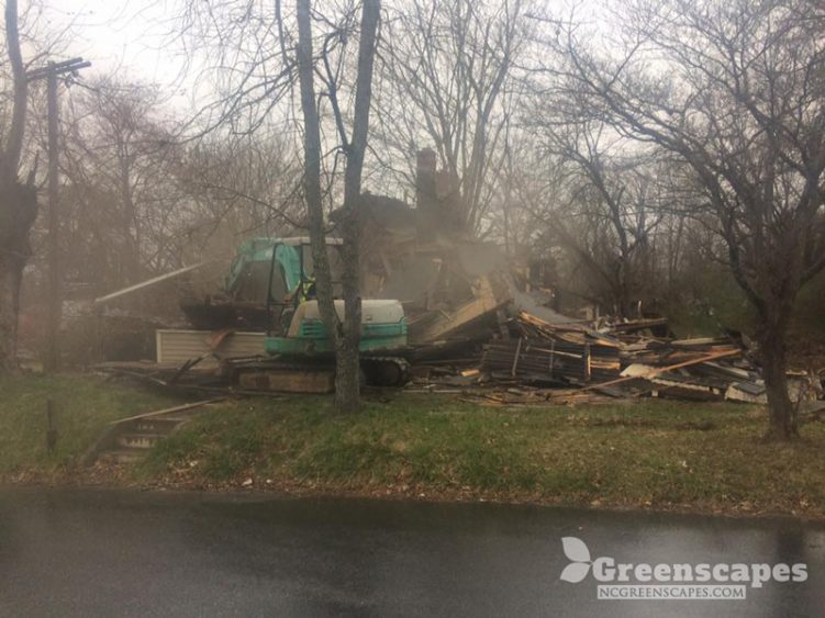 heavy equipment contractor breaking down large home that was  burned