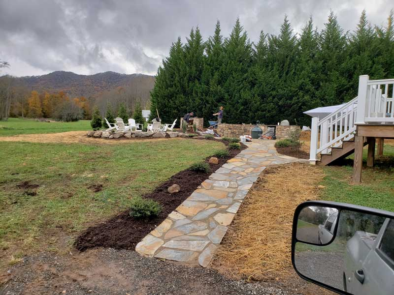 newly paved walkway with landscaping leading to an outdoor kitchen and firepit