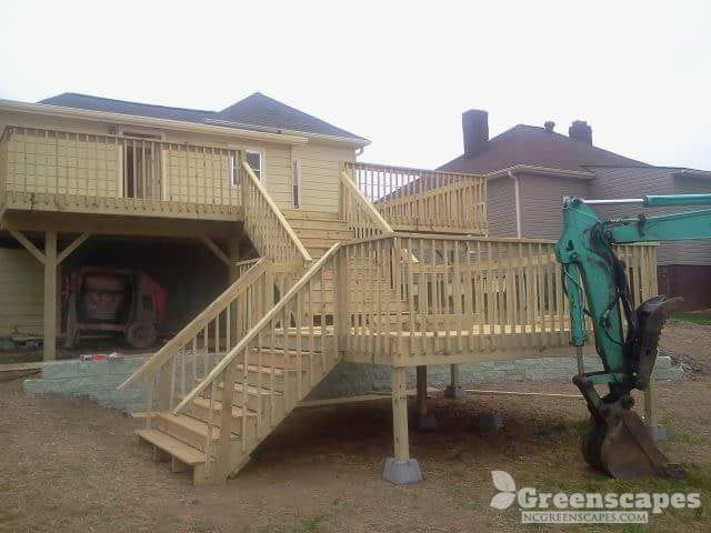 Outdoor carpentry contractor just built brand new multi-level deck added on the back of a two story home
