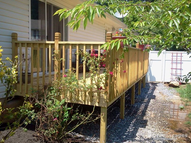 pressure treated wooden deck with plants and flowers laying on it