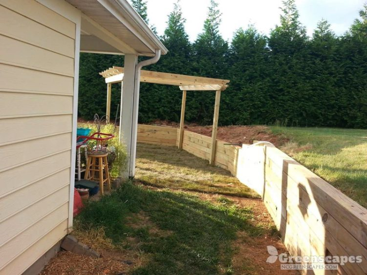 freshly build pergola in the back yard with a wood retaining wall