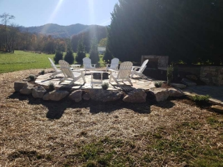 Hot sun shining down on 6 white chairs around firepit