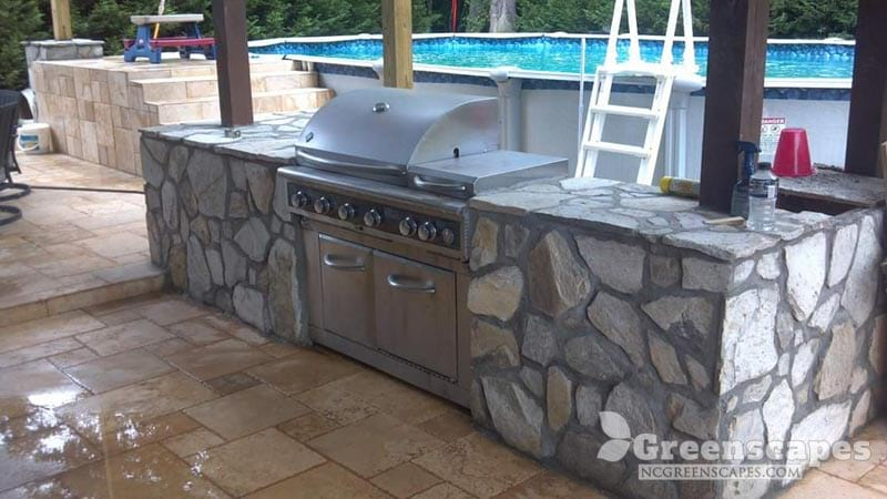 Stone counters for outdoor kitchen space with a large metal grill and pool in the background