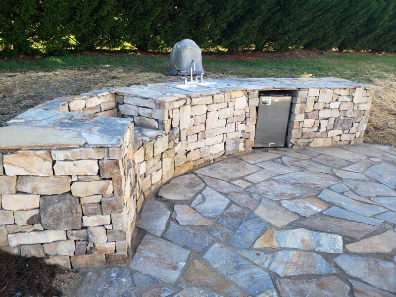 natural stone outdoor kitchen counter with green egg placement, sink and cooler