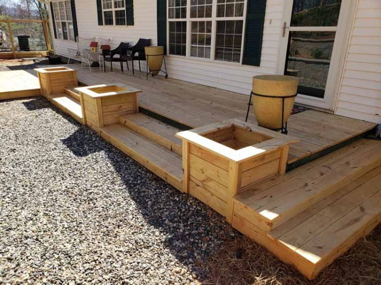 newly completed honey wood deck on front of house with 3 wooden planters