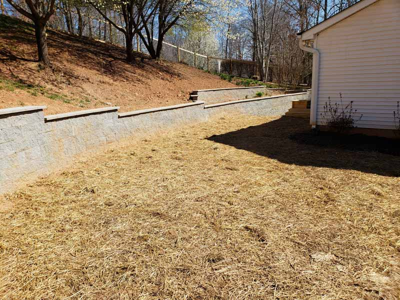 fertilized grass surrounding a newly completed block retaining wall