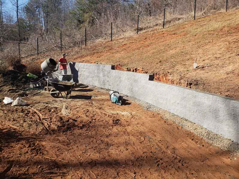 man laying block retaining wall cutting off side of mountain while sun beaming down