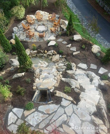 stone pathway leading down a waterfall and into a stone patio seating area with fire pit